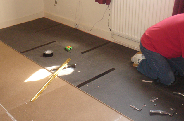 Installing QuietFloor Plus onto a floor with taped joints